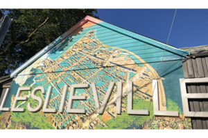 """A picture of a mural on the side of a garage. Across the mural reads, """"Leslieville"""". The mural itself features a map of Leslieville in bright blues and yellows."""