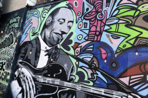 A picture of a mural featuring a man playing guitar. Around him vibrant colours and bold linework give the impression of rhythm and music.