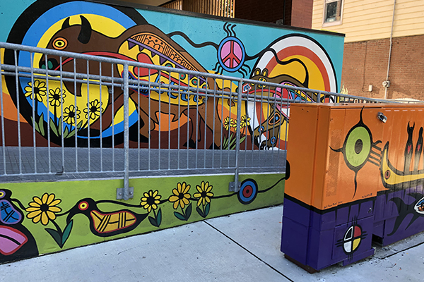 A exterior shot of a concrete ramp with a metal railing, in front of it sits an electrical box. The box and ramp are painted in bright Indigenous-style scenes. A buffalo and duck feature prominently.