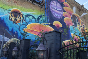 A picture of a mural on the side of a building. Fuzzy bumblebees fly across a blue background that features dark blue cogs. There is a purple and shiny clock and vibrant orange fungi growing up a tree trunk.