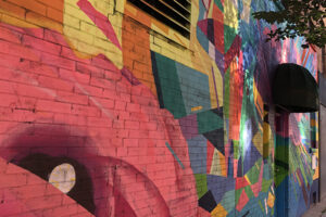 A picture of a mural. The art is vibrant and colourful featuring abstract shapes across the wall.