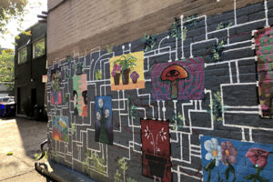 A photo of a mural on the side of a building. The mural features multiple smaller illustrations all interconnected with white lines that look like circuitry. The background is gray.