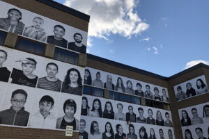A picture of a side of a school. Across the walls are pasted 200 black and white portraits of students.