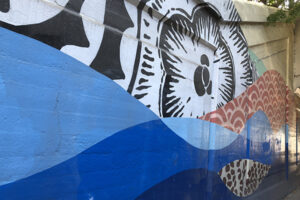 A picture of a mural on the side of an underpass. There are a blue waves and a red wave featuring a decorative pattern. Above the waves a black and white flower-type shape is painted in bold linework.