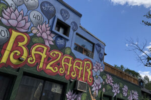 """A picture of a colourful mural on the side of a building. In bold yellow letters reads, """"Bazaar"""". Pink lotus flowers are painted throughout the mural."""