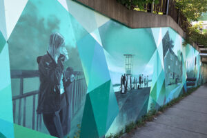 A picture of a mural on the side of an underpass. In prismatic blues there are several outdoor scenes painted. In one, a person leans against a metal railing drinking a coffee, in another there is a beach scene.