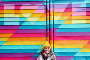 """A picture of a woman in a yellow hat in front of a colourful mural. She is smiling. The mural is a bright rainbow and in lighter block leaders it reads, """"Love""""."""