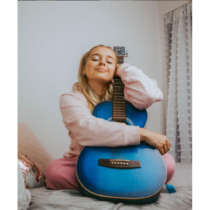 A Photo Of Millie Bee. She's Sitting Cross-legged On A Bed Hugging A Blue Guitar. Her Eyes Are Closed And Head Tipped Back, Leaning Against The Neck Of The Guitar.