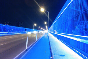 A picture of the Luminous Veil lit up a night. It is a bridge, bordering the edges is a wire wall lit up bright blue.